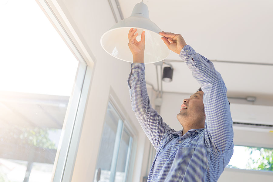 Asian man changing a light bulb at home and installing an energy efficient LED light bulb