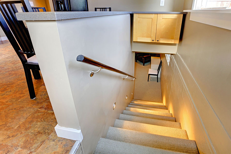 Basement stairs with handrail and spotlights