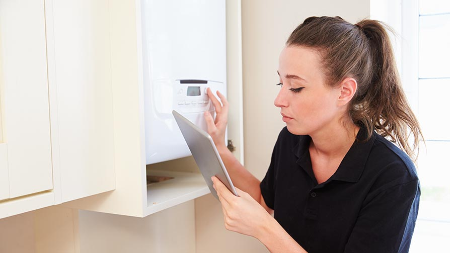 Female technician servicing a new boiler using a tablet computer