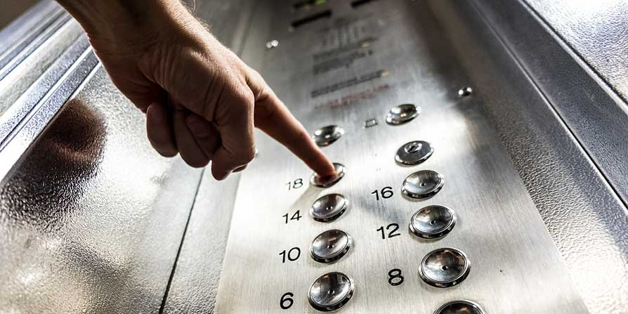 View of a person's finger pressing a button in a lift