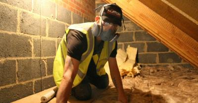 Builder laying glass wool insulation in a roof cavity